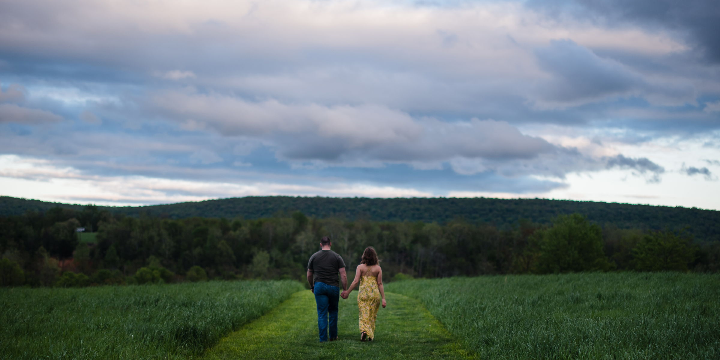 A couple walks through a summer field during their Harpers Ferry engagement photos