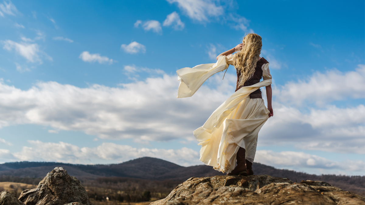 Cosplayer dressed as Eowyn from Lord of the Rings stands on a rock facing mountains at Blue Valley Vineyard