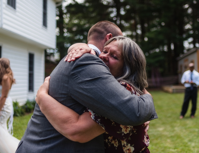 A son hugs his mother during a mother-son dance at a small backyard wedding ceremony in Maryland