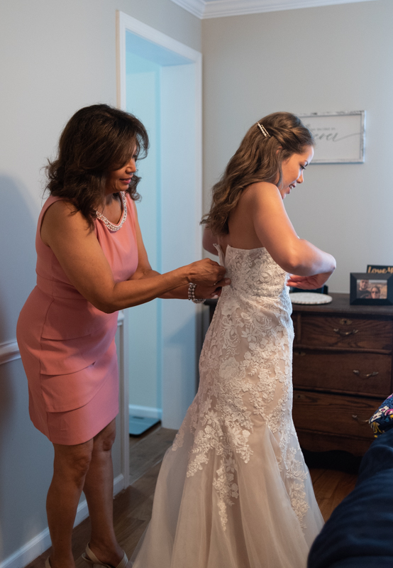 Mother helps daughter into her wedding dress during a small backyard wedding in Maryland