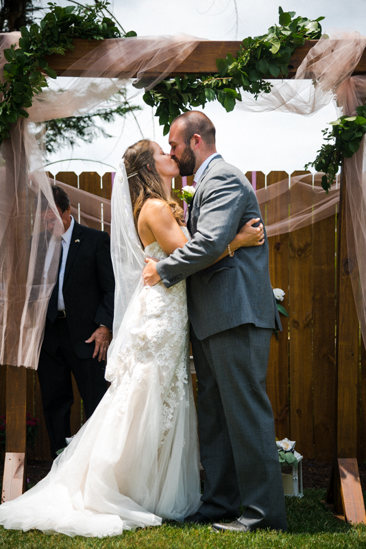 Bride and groom have their first kiss during a small backyard wedding ceremony