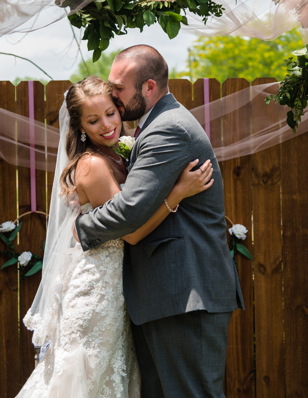 Grooms kisses bride on the forehead after saying their vows during their Maryland backyard ceremony