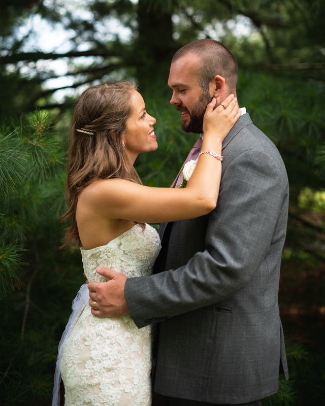 Wedding couple poses in front of a tree in their backyard during their backyard wedding