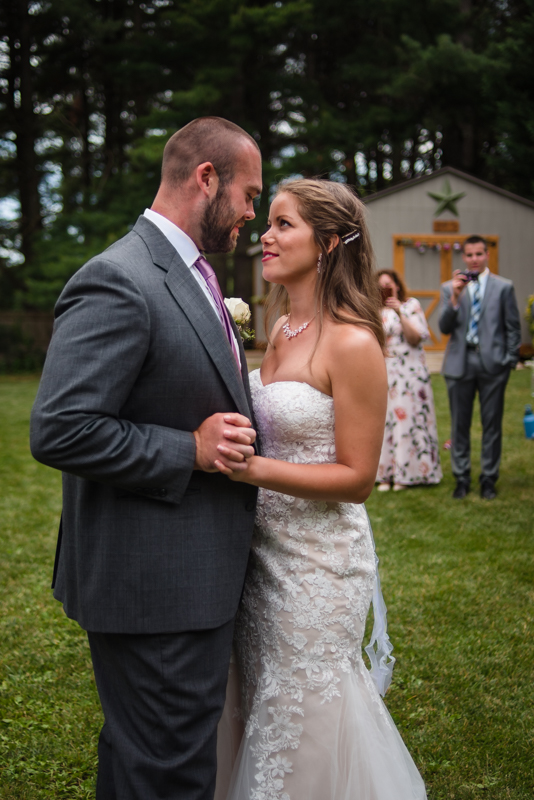 Bride and groom dance while their family watches during their intimate backyard maryland wedding