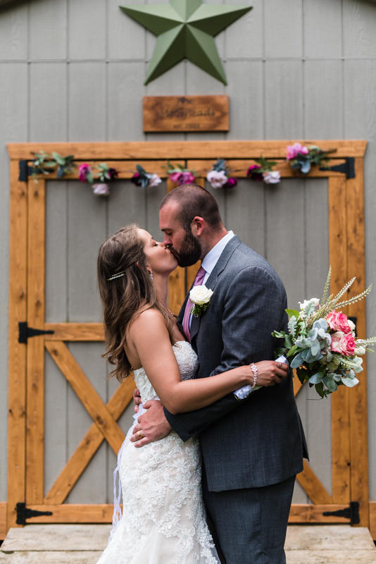 Bride and groom kiss in front of their shed during their Maryland backyard wedding