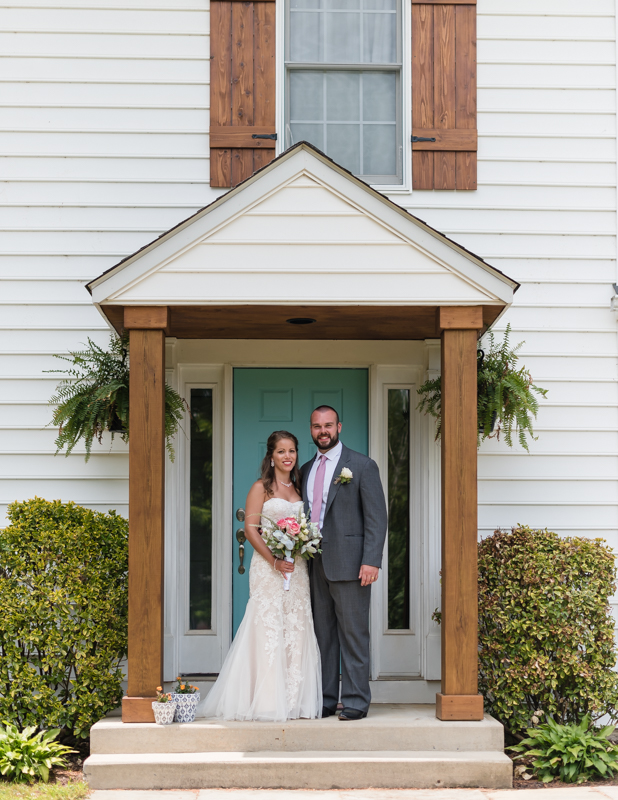 Bride and groom pose in front of their home after their intimate backyard wedding ceremony in Maryland.