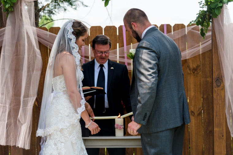 Bride and groom light the unity candle at their intimate backyard wedding in Maryland.