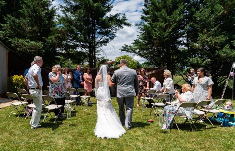 Father escorts his daughter down the aisle at a small backyard wedding in Maryland
