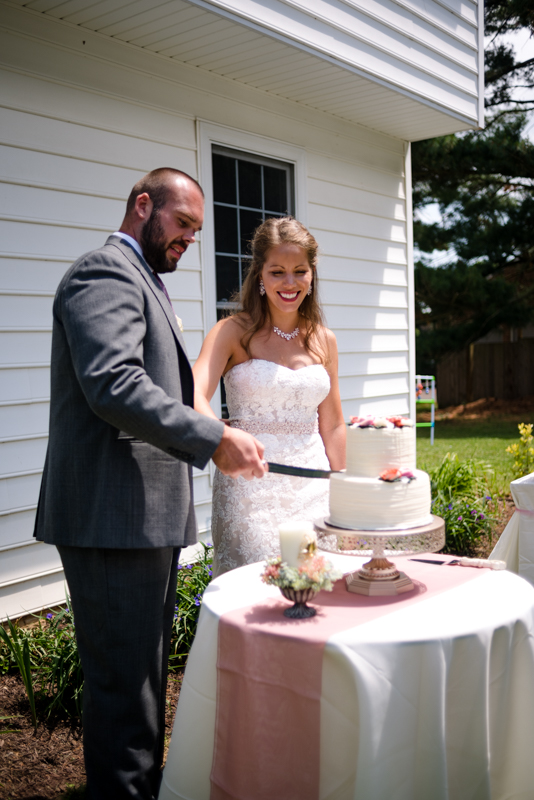Bride and groom cut their wedding cake at their intimate backyard wedding in Hagerstown, Maryland.
