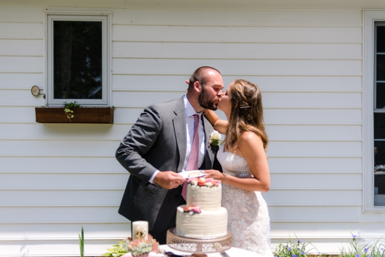 Bride and Groom kiss after cutting up their wedding cake during their backyard wedding
