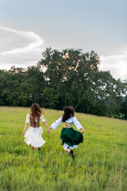 Two girls in renaissance faire costumes run through a sunlit field in Harpers Ferry