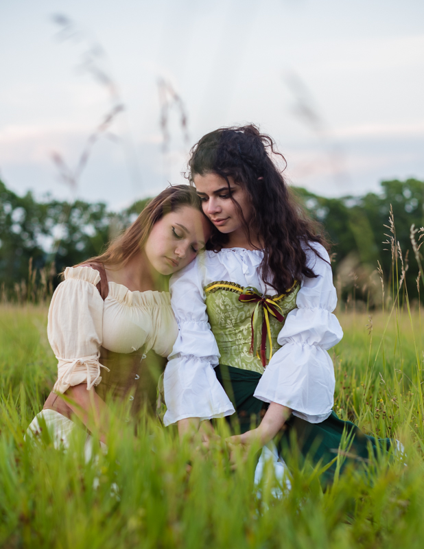 A couple sits together in a field while wearing renaissance costumes in harpers ferry, west virginia