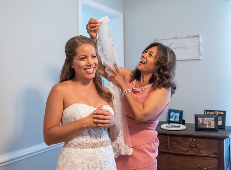 A mother and daughter laugh together while getting ready before a small backyard wedding ceremony in Maryland