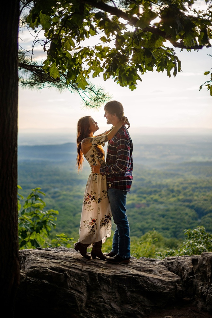 A couple smile at each other while posing for their engagement photos at Bears Den Overlook in Virginia