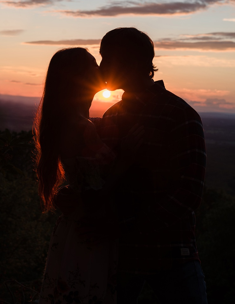 A couple is kissing silhouetted against the sunset at Bears Den Overlook in Virginia