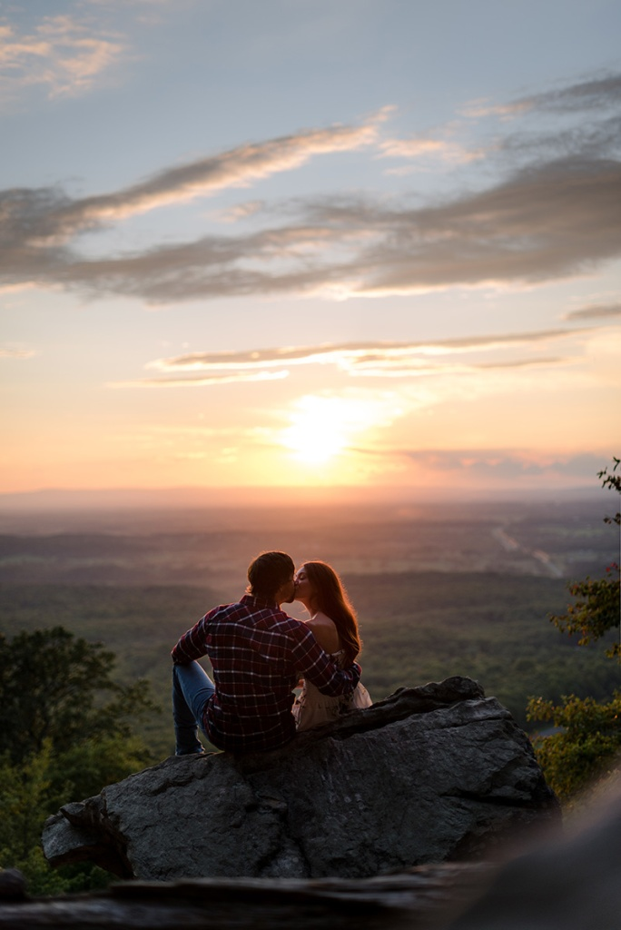 A couple kiss while watching the sunset at Bears Den Overlook in Virginia