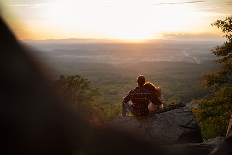 A couple sits together watching the sunset at Bears Den Overlook in Bluemont, Virginia