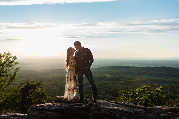 A couple stands against the backdrop of Bears Den Overlook in Bluemont, Virginia for their engagement session