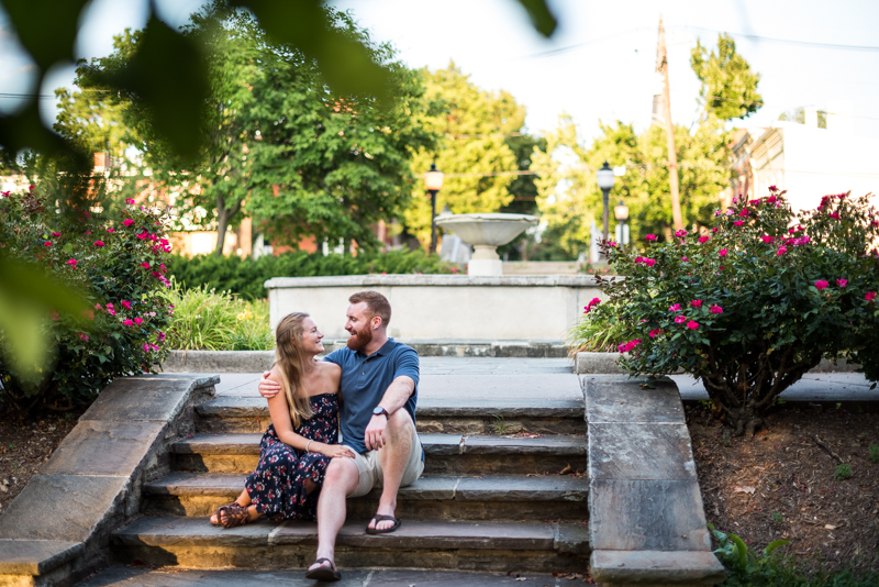 A couple laughs together on steps leading up to a foundation during their engagement photo session at Baker Park