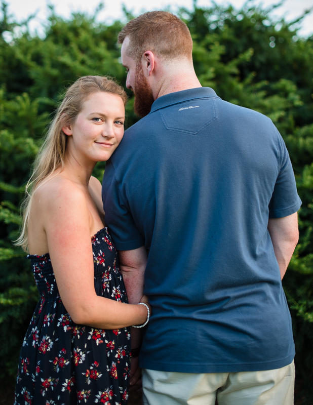 A woman looks at the camera while her fiancé looks at her for engagement photos