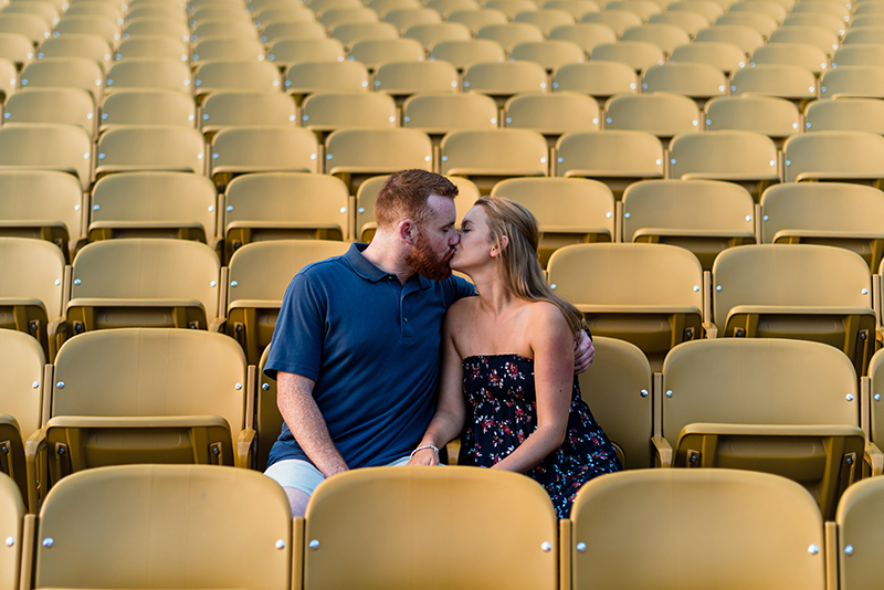 A couple kisses while sitting down at the bleachers at Baker Park for their Frederick Maryland engagement photos
