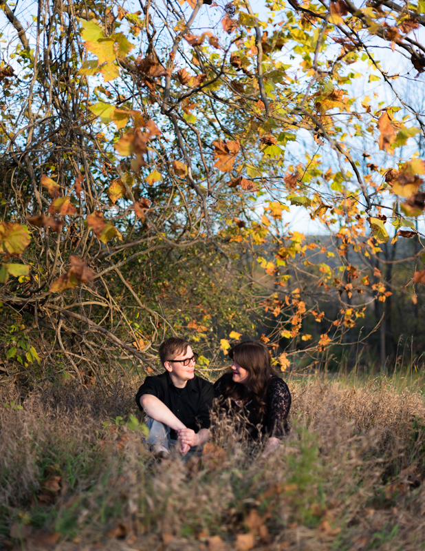 A couple is framed by fall leaves during their fall engagement session