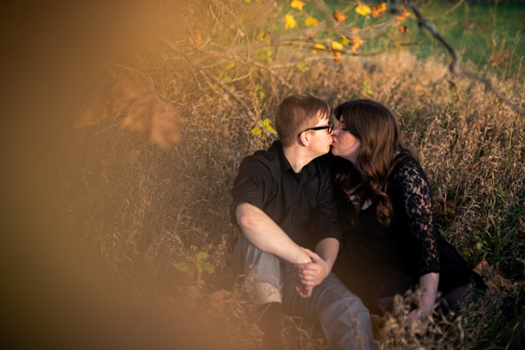 A couple kisses under a fall tree during their fall engagement session in West Virginia