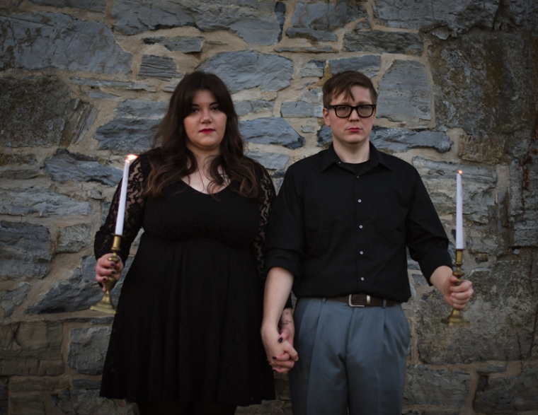 A couple looks at the camera while holding candles during their Halloween Engagement photoshoot