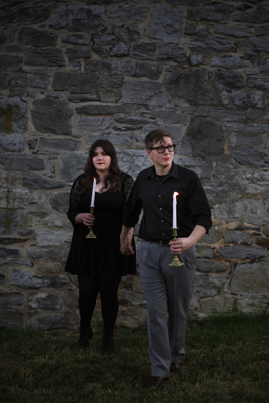 A couple walks towards the camera while holding candles during their Halloween Engagement photoshoot