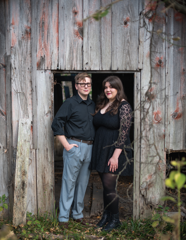 A couple stands in the doorway of an old shed for their engagement photos in Harpers Ferry