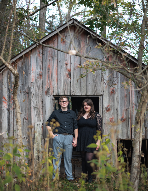 A couple stands and looks at the camera during their engagement photo session in Harpers Ferry, West Virginia