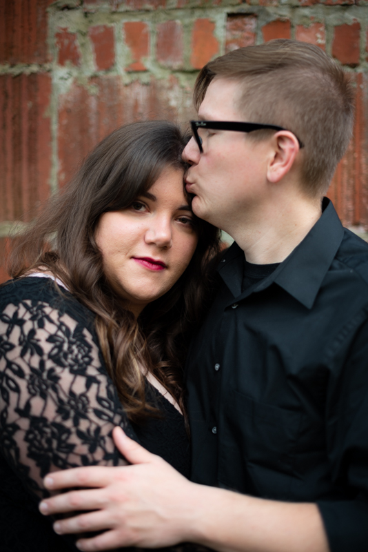 A man kisses his fiancee's head during their spooky engagement photo session in Harpers Ferry, West Virginia