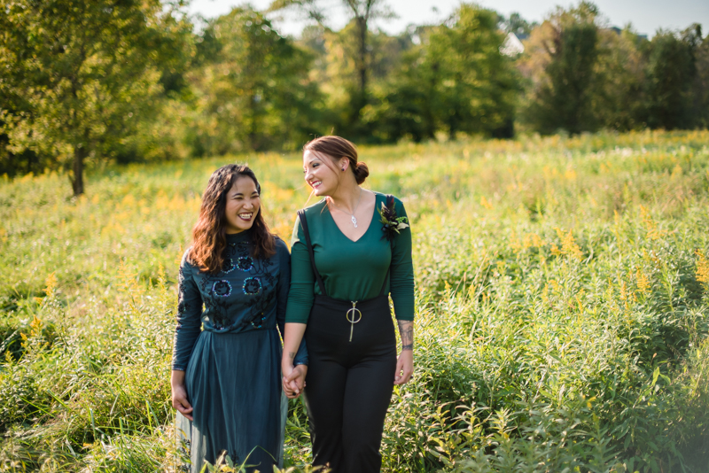 Two brides walk together in a field for couples' portraits at Ballenger Farm in northern virginia