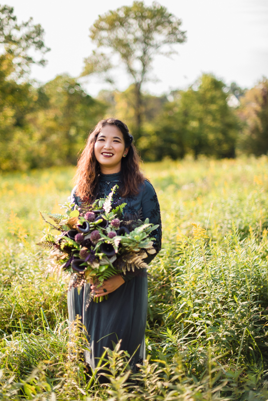 A bride poses in a field in a black dress for her bridal portraits during her offbeat wedding in northern virginia