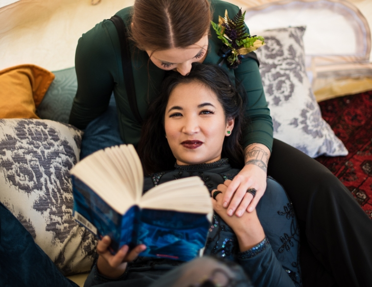 Two brides sit in a tent together while one reads a Harry Potter book during their offbeat wedding at Ballenger Farm