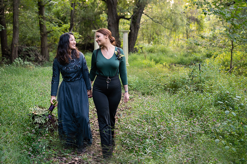 Two brides walk together in a field at Ballenger Farm during their offbeat wedding