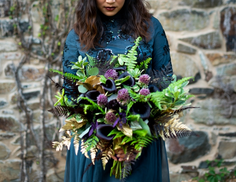 A bride poses with her bouquet in a black dress for her bridal portraits during her offbeat wedding in virginia