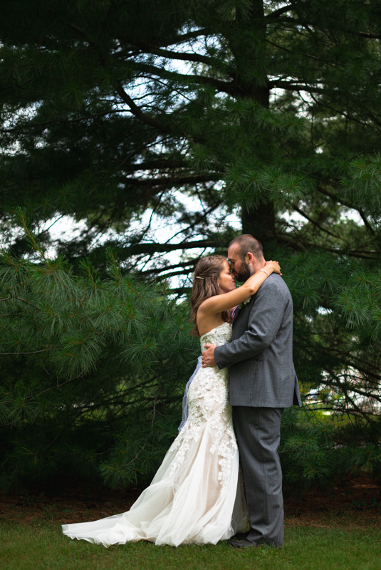 A husband and wife give each other a kiss under a tree during their backyard wedding ceremony
