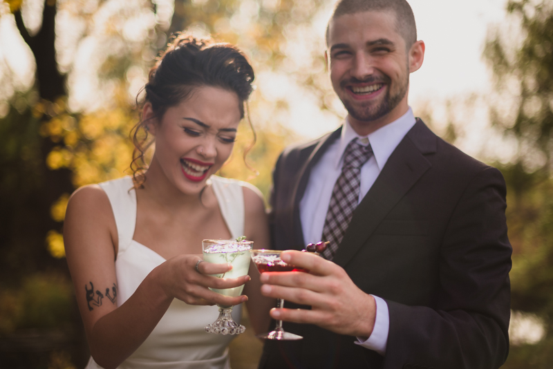 A husband and wife clink their glasses together during their wedding at Ballenger Farm