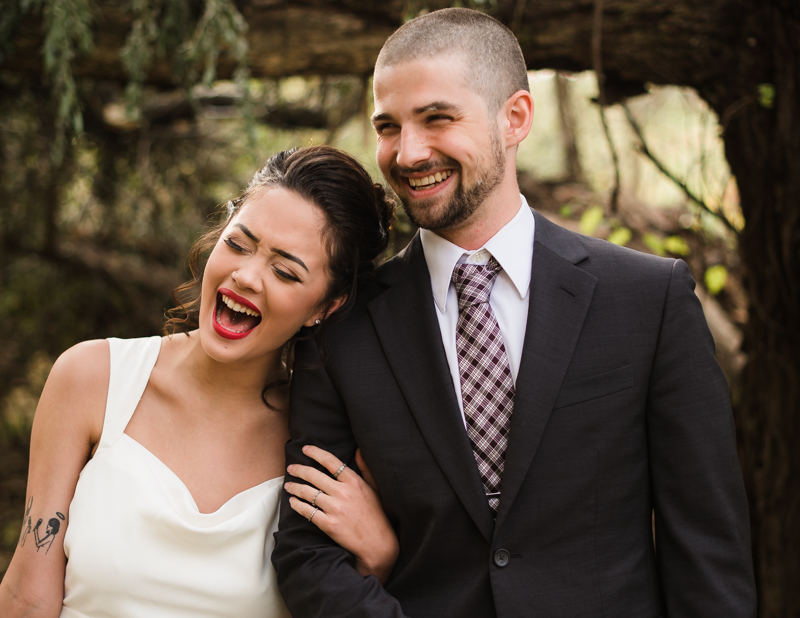 A husband wife laugh together during their wedding at Ballenger Farm
