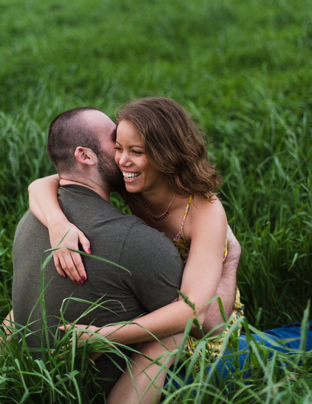 A woman laughs with her fiancee while sitting in the grass in Harpers Ferry, West Virginia