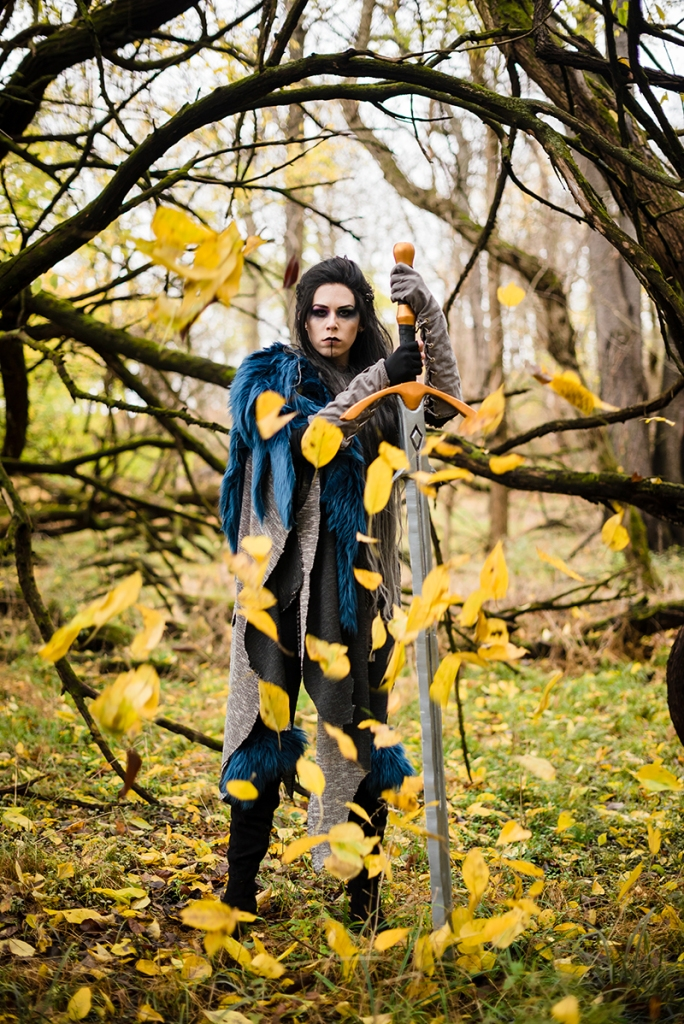 A woman dressed in a Yasha Cosplay from Critical Role stands in a fall forest while leaves swirl around her