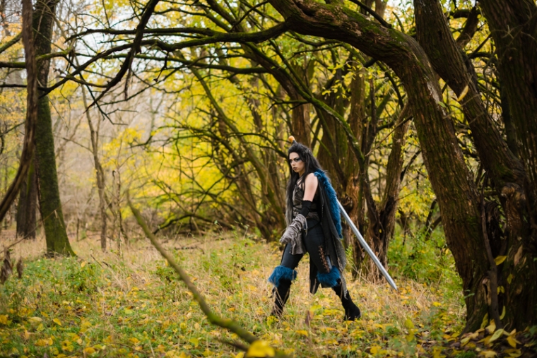 A woman dressed in a Critical Role Cosplay walks out from behind a tree in a fall forest