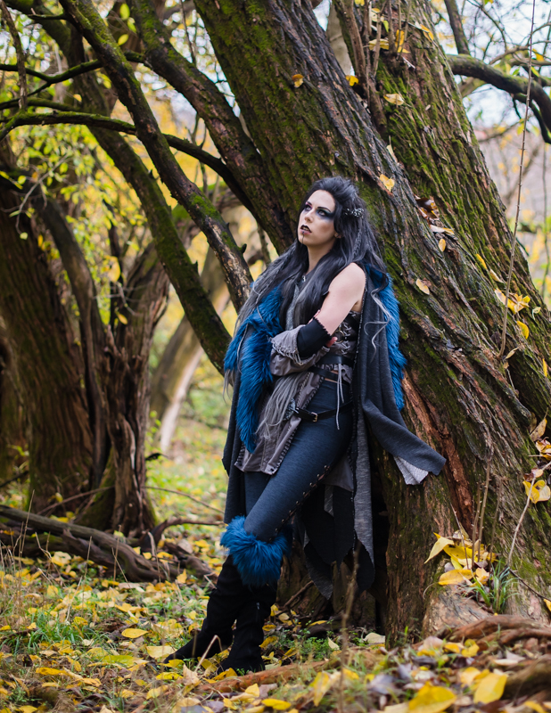 A woman dressed in a Critical Role Cosplay leans against a tree in a fall forest
