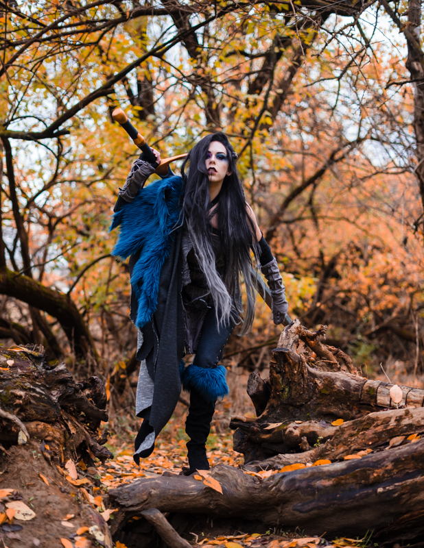 A woman dressed in a Yasha Cosplay from Critical Role walks over a log in a fall forest