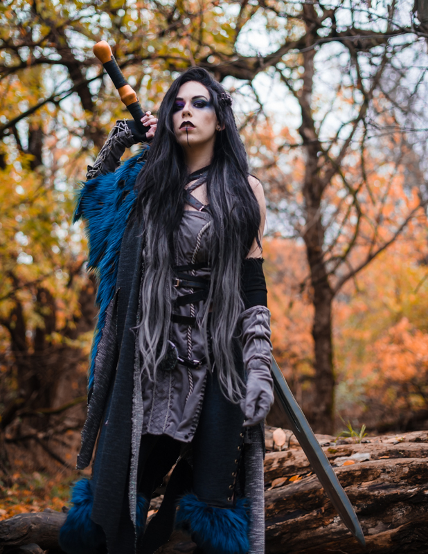 A woman dressed as Yasha from Critical Role stares down at the camera in a fall forest