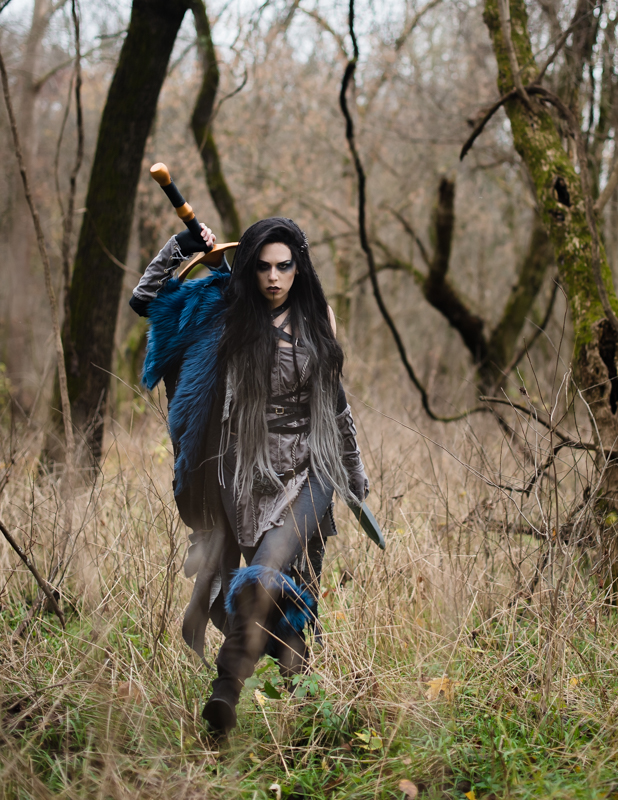 A woman dressed in a Yasha Cosplay from Critical Role runs through the woods
