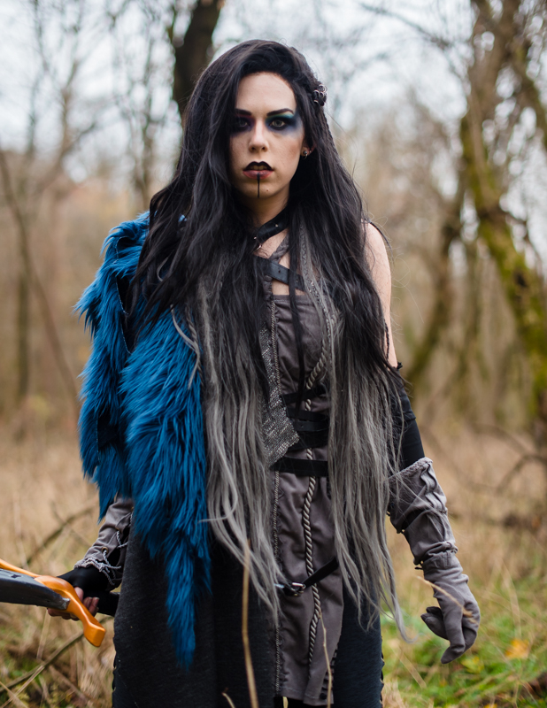 A woman dressed in a Critical Role Cosplay walks through the woods