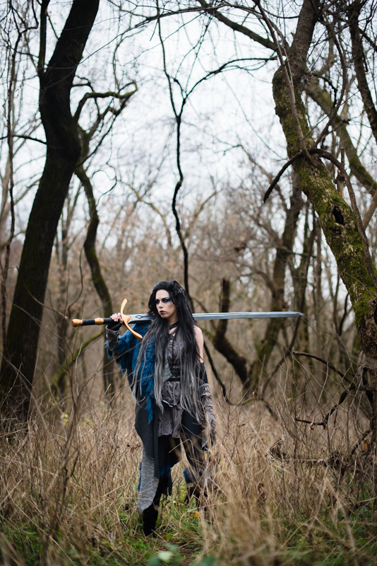 A woman dressed in a Yasha Cosplay from Critical role stands in the woods with her giant sword over her shoulder