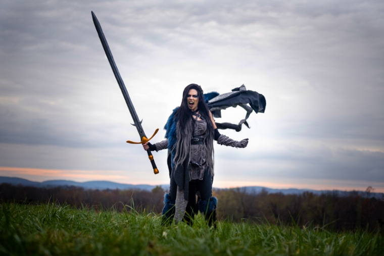 A woman dressed as Yasha from Critical Role screams at the sky with her cape blowing out behind her